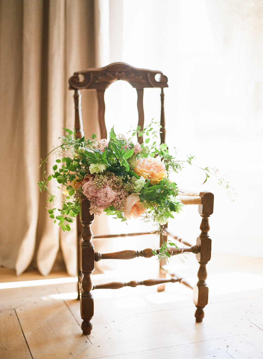 Afternoon light bathes a wooden chair and a gorgeous, rustic bouquet at the 2016 Workshops in Burgundy; photo by Sylvie Gil