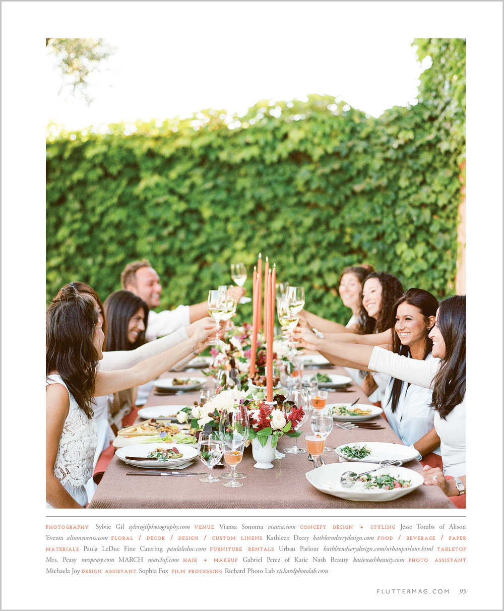 The party guests toast at a beautifully decorated table in Flutter Magazine; Sylvie Gil Photography