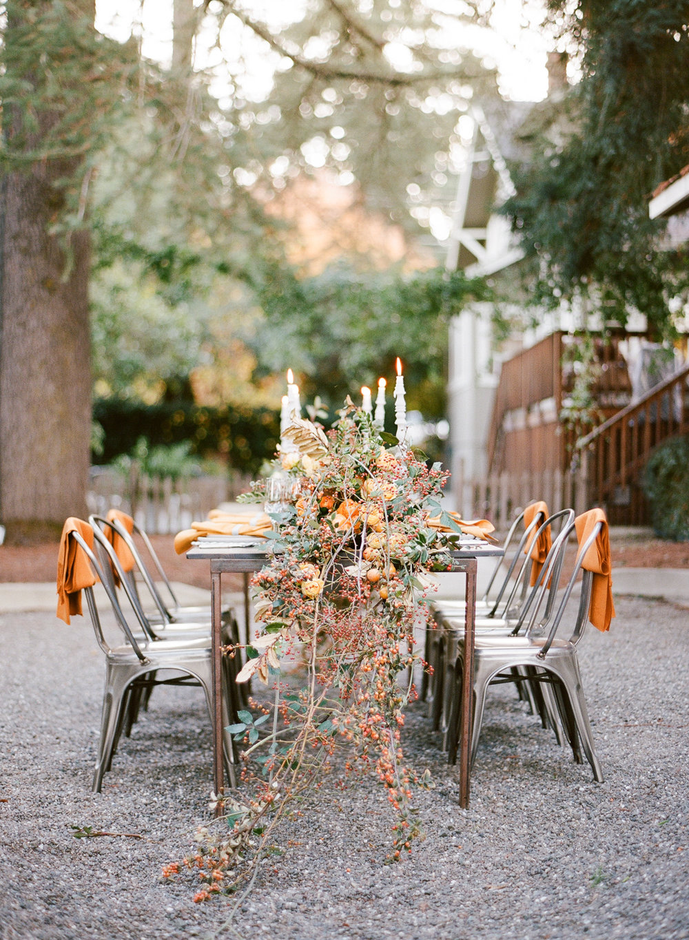 Cascading table garland consisting of wild rosehip, blackberry, and cotoneaster vines mixed with orange and yellow peonies and ranunculus; Sylvie Gil Photography