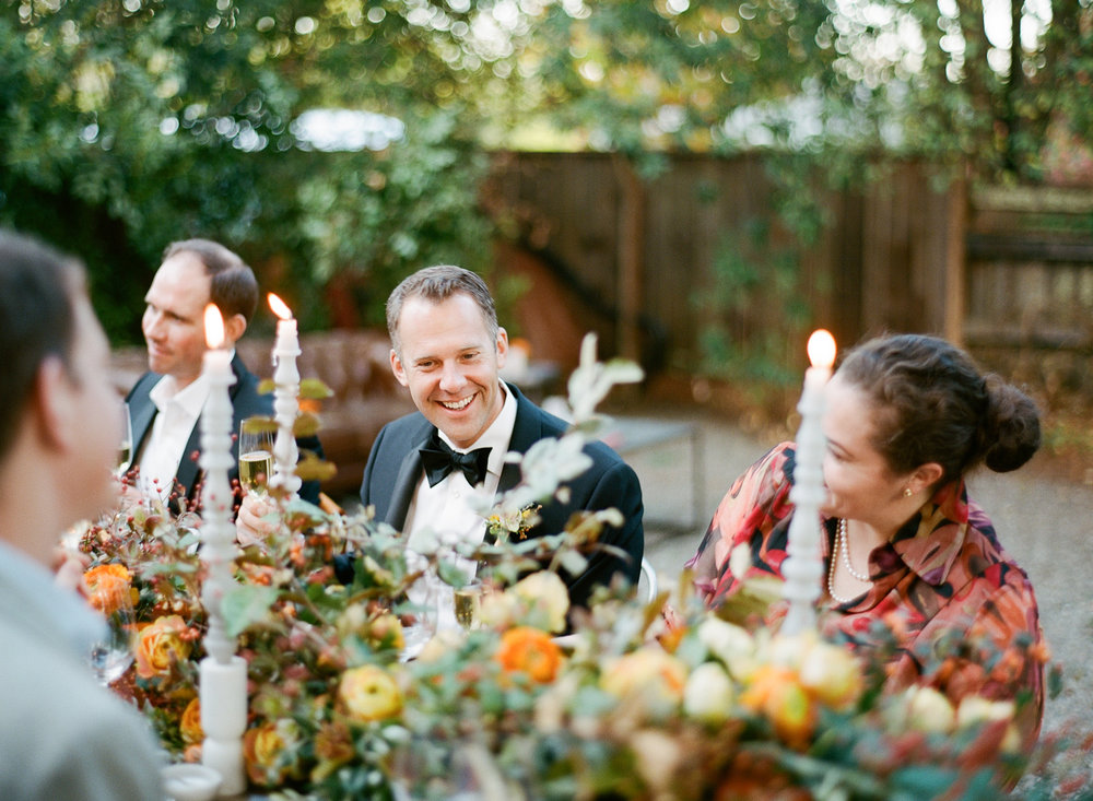Guests and grooms share an outdoor reception dinner by candlelight in St. Helena; Sylvie Gil Photography