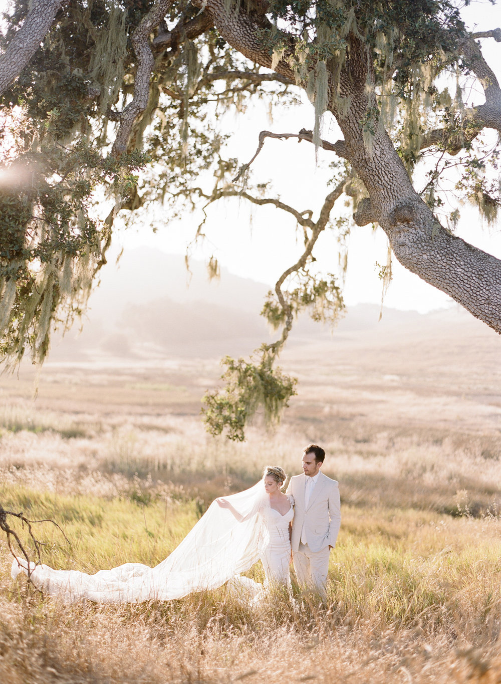 The couple stands underneath a tall oak in the Santa Lucia preserve at sunset; Sylvie Gil Photography