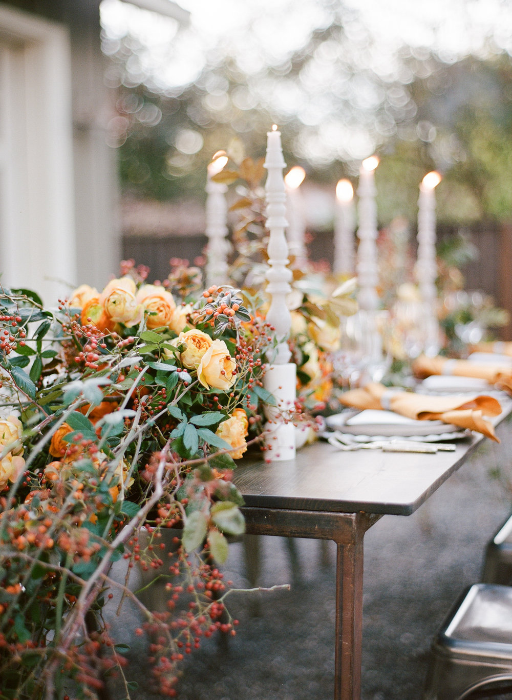 A wild orange floral wreath and tall white candelabras on the outdoor reception table; Sylvie Gil Photography