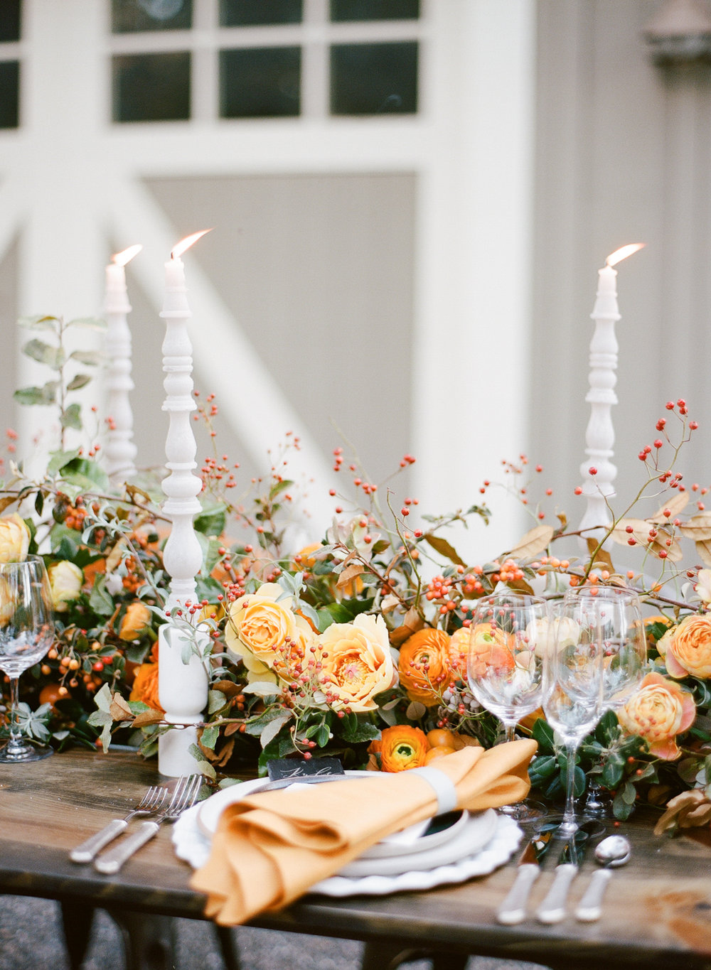 Floral table garland centerpiece of rosehip and blackberry vines, yellow peonies, and orange ranunculus; Sylvie Gil Photography