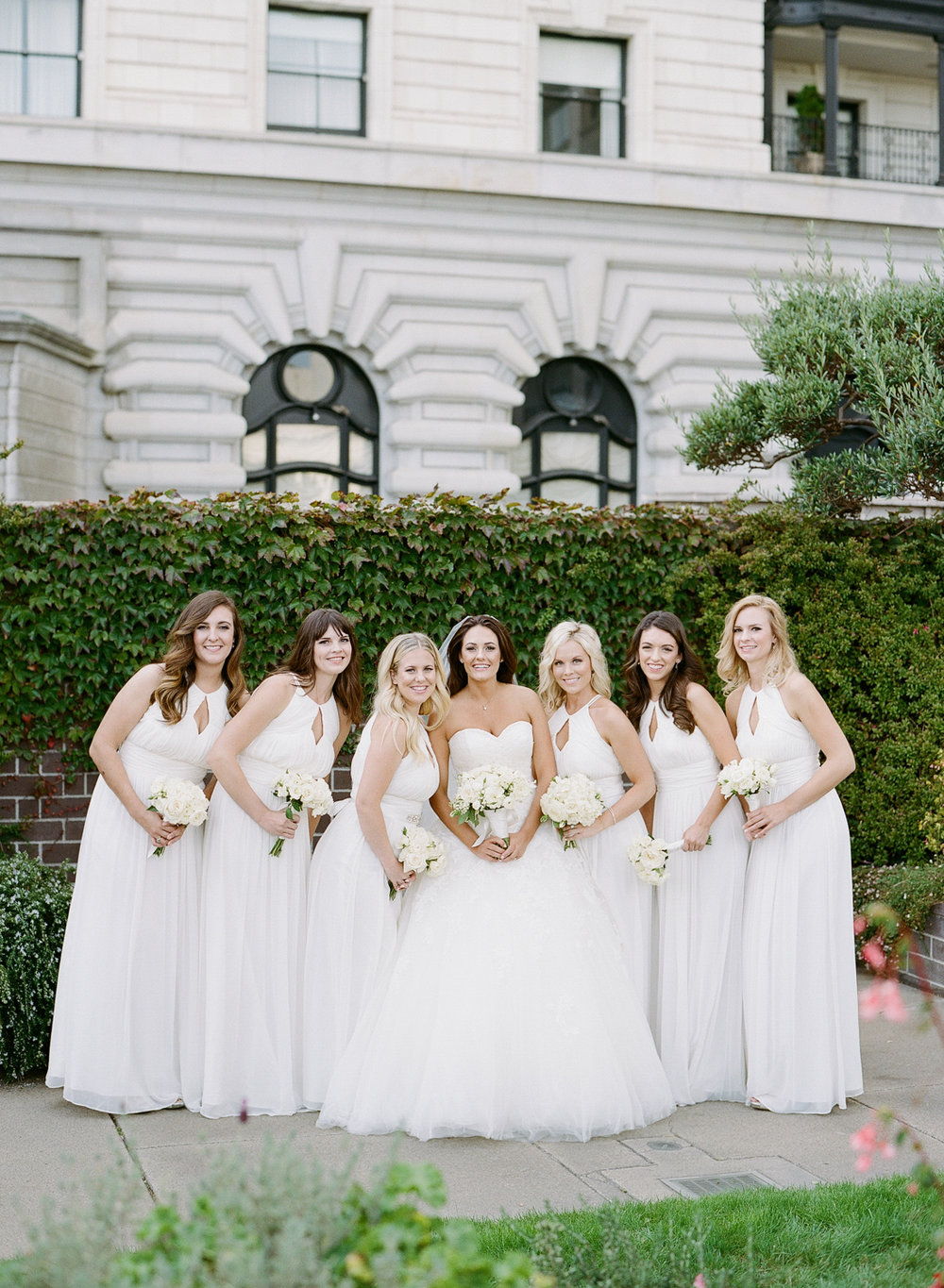 The bridesmaids lean in, dressed in elegant white gowns, for a bridal party shoot; photo by Sylvie Gil