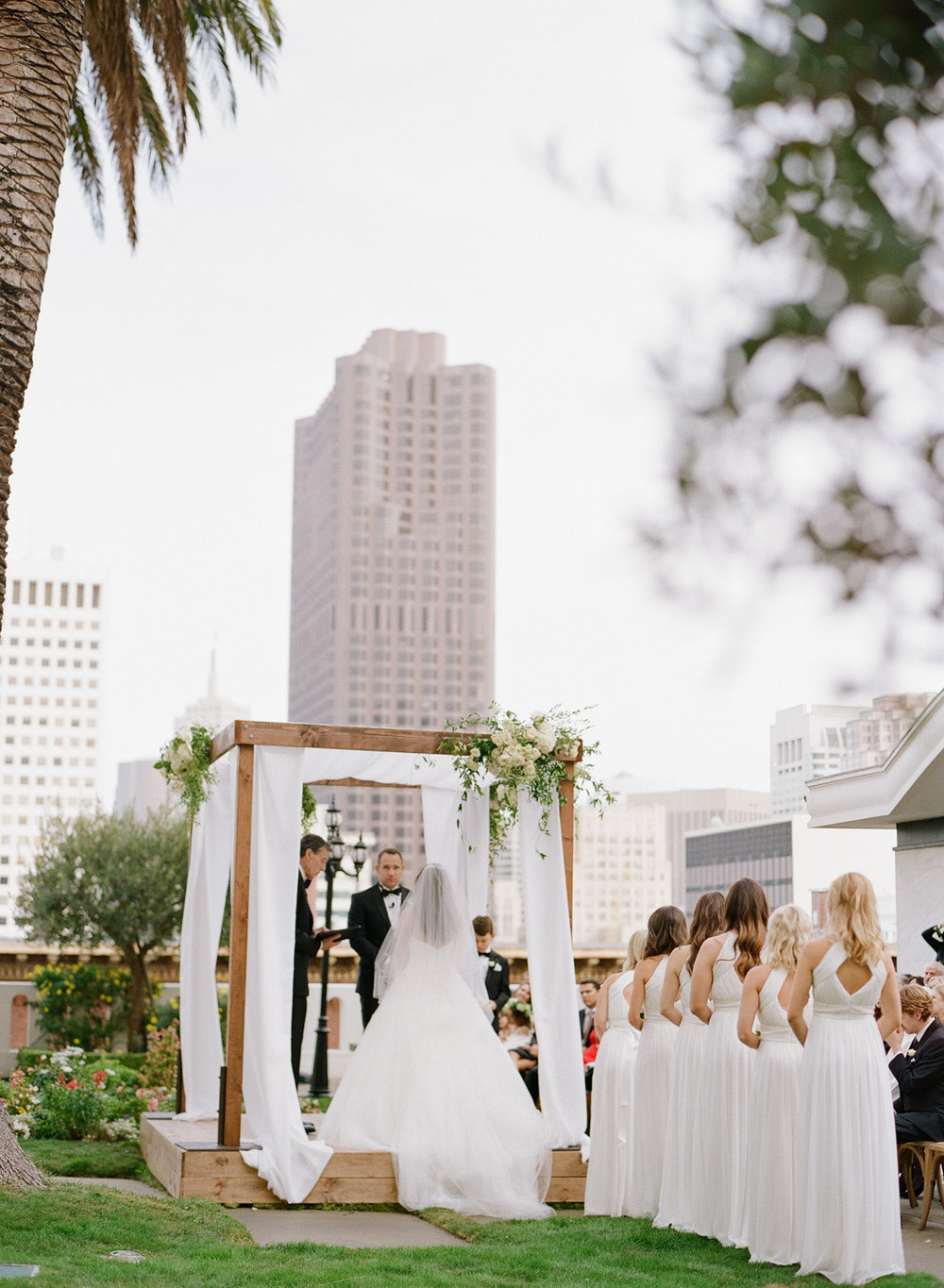 A row of bridesmaids in white gowns look on while Meg & Ben exchange vows under a floral arbor; photo by Sylvie Gil