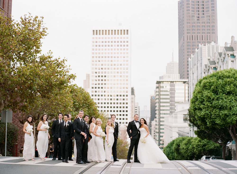Meg & Ben, along with their bridal party, posing for a unique shot in the middle of a San Francisco crosswalk, on top of streetcar tracks; photo by Sylvie Gil