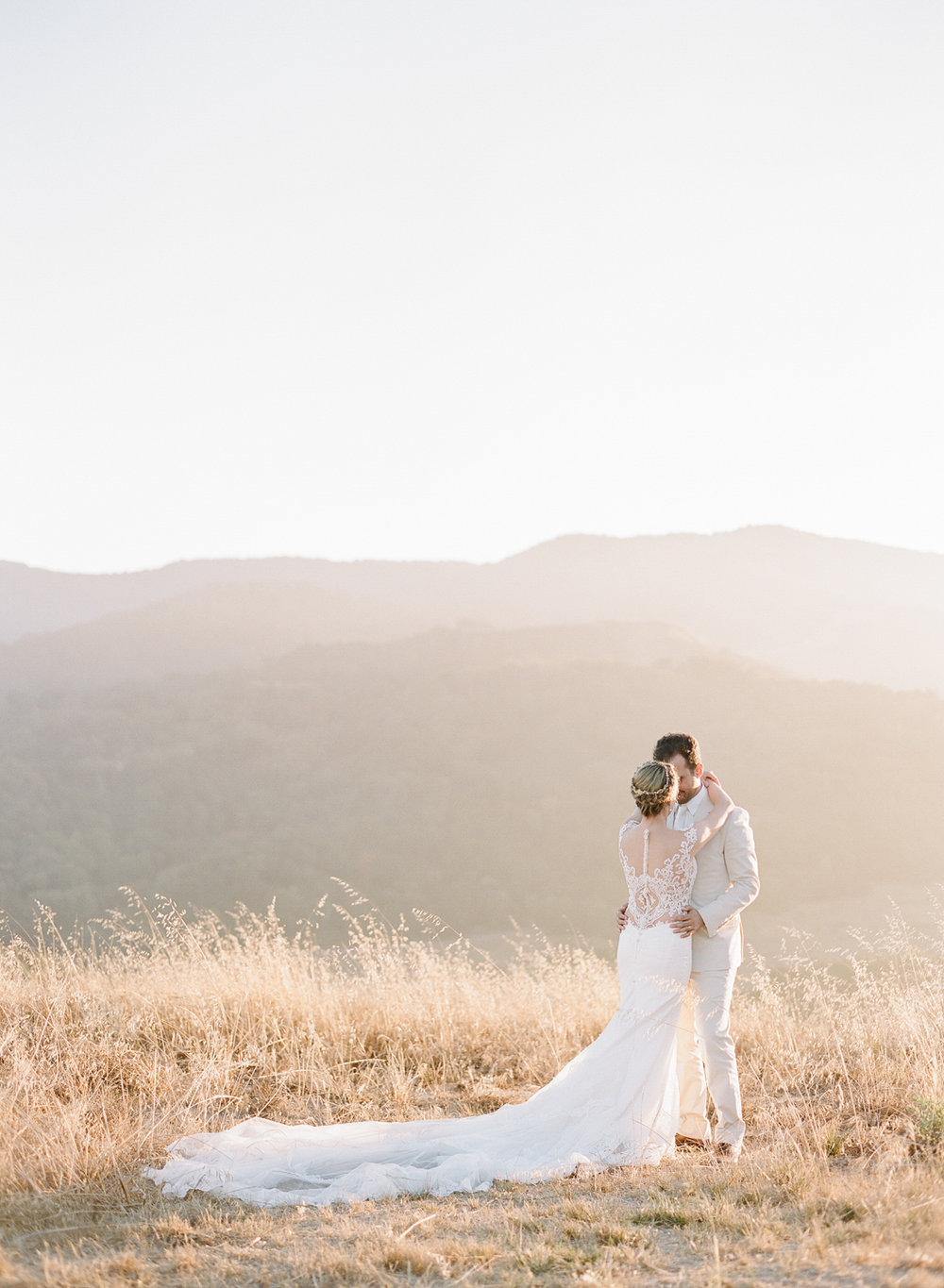 Bride and groom share a romantic moment in a grassy field at sunset; Sylvie Gil Photography