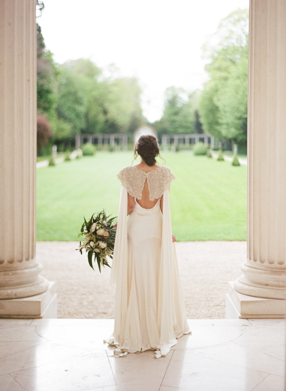 The bride stands between columns outside Pavillon de la Musique in Paris; Sylvie Gil Photography