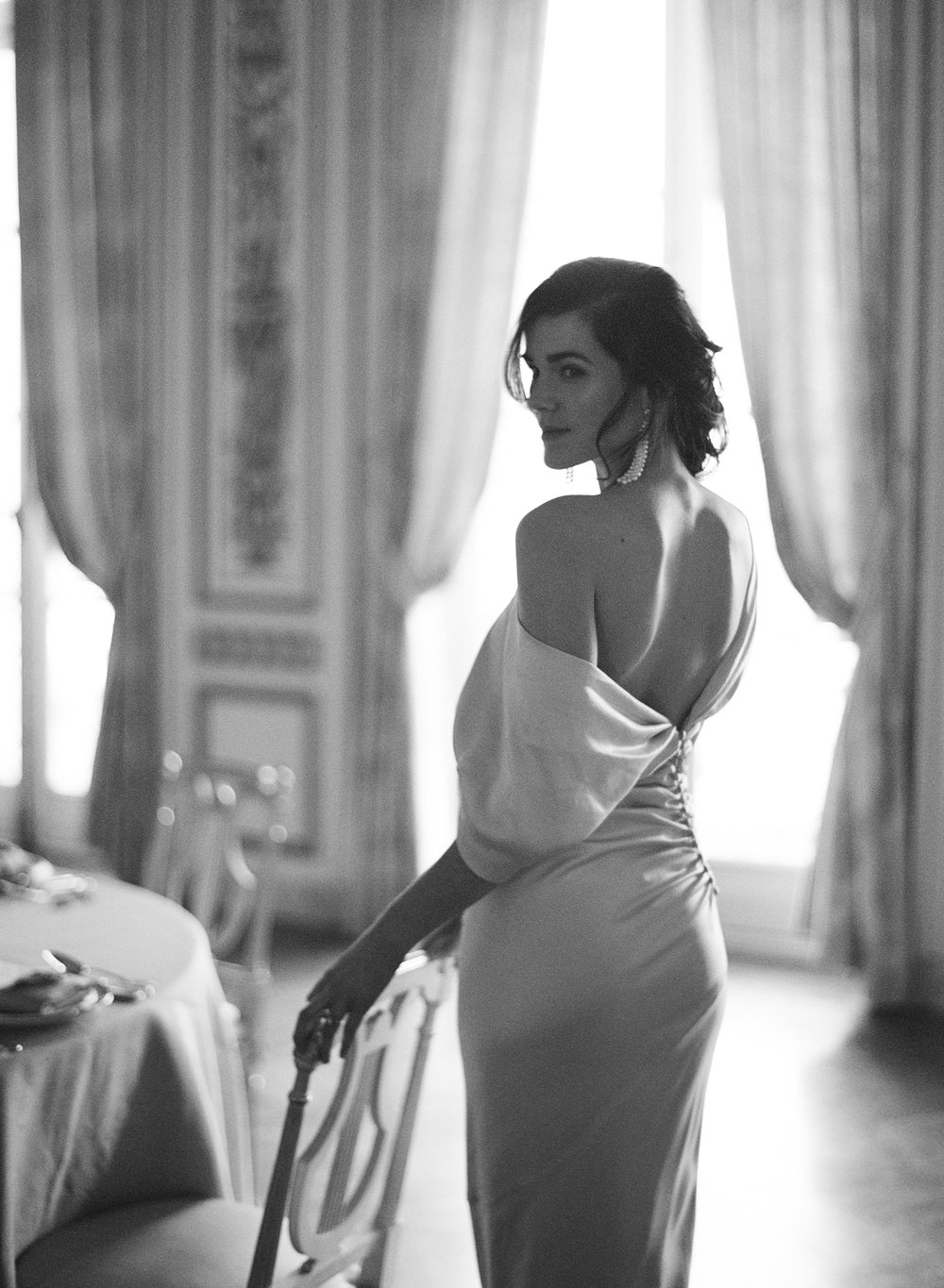 Bride dressed in an elegant asymmetrical, off-the-shoulder gown and elegant pearl earrings; Sylvie Gil Photography