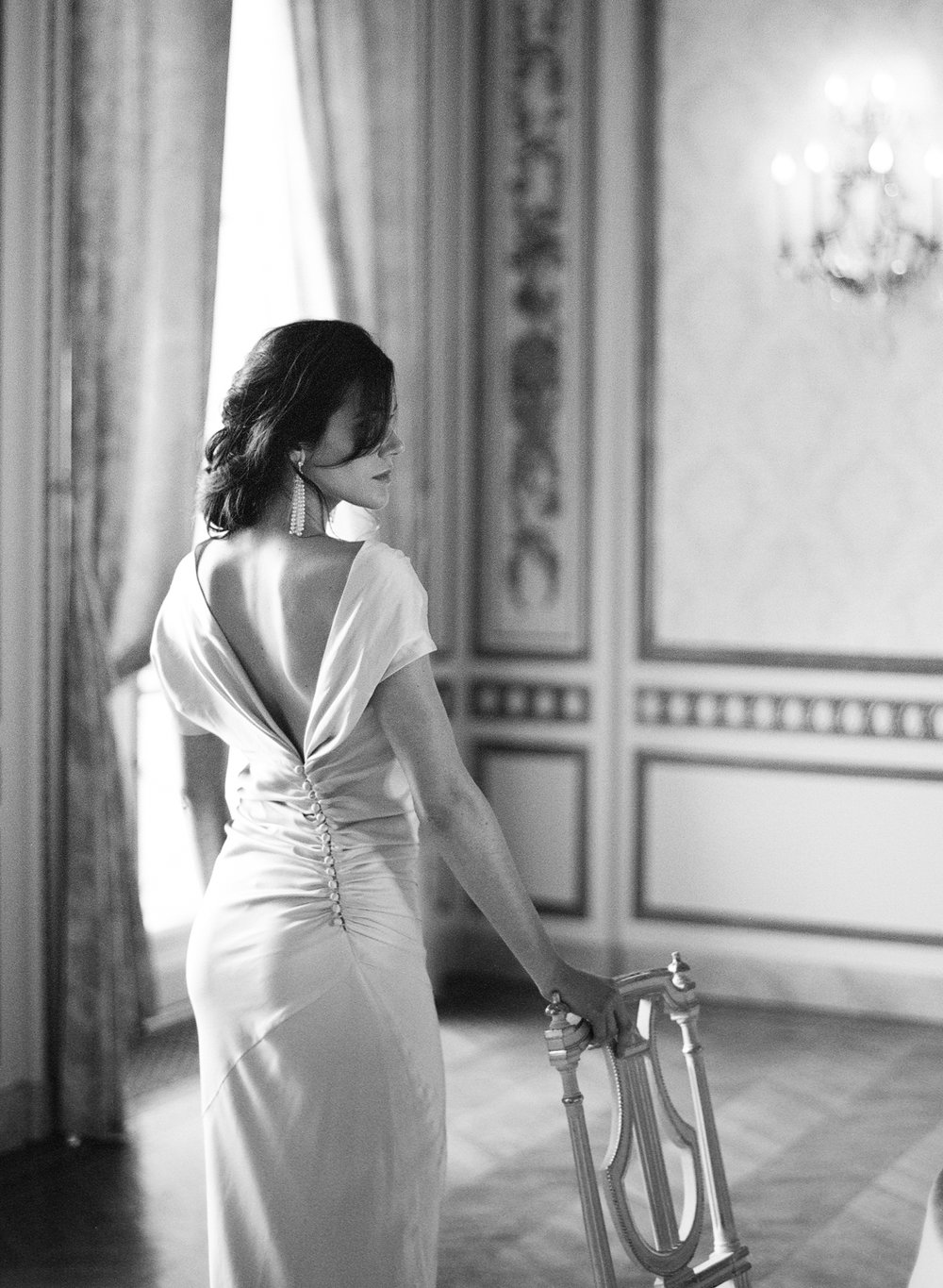 The bride in an asymmetrical Houghton Bride dress stands at the vintage French reception table; Sylvie Gil Photography