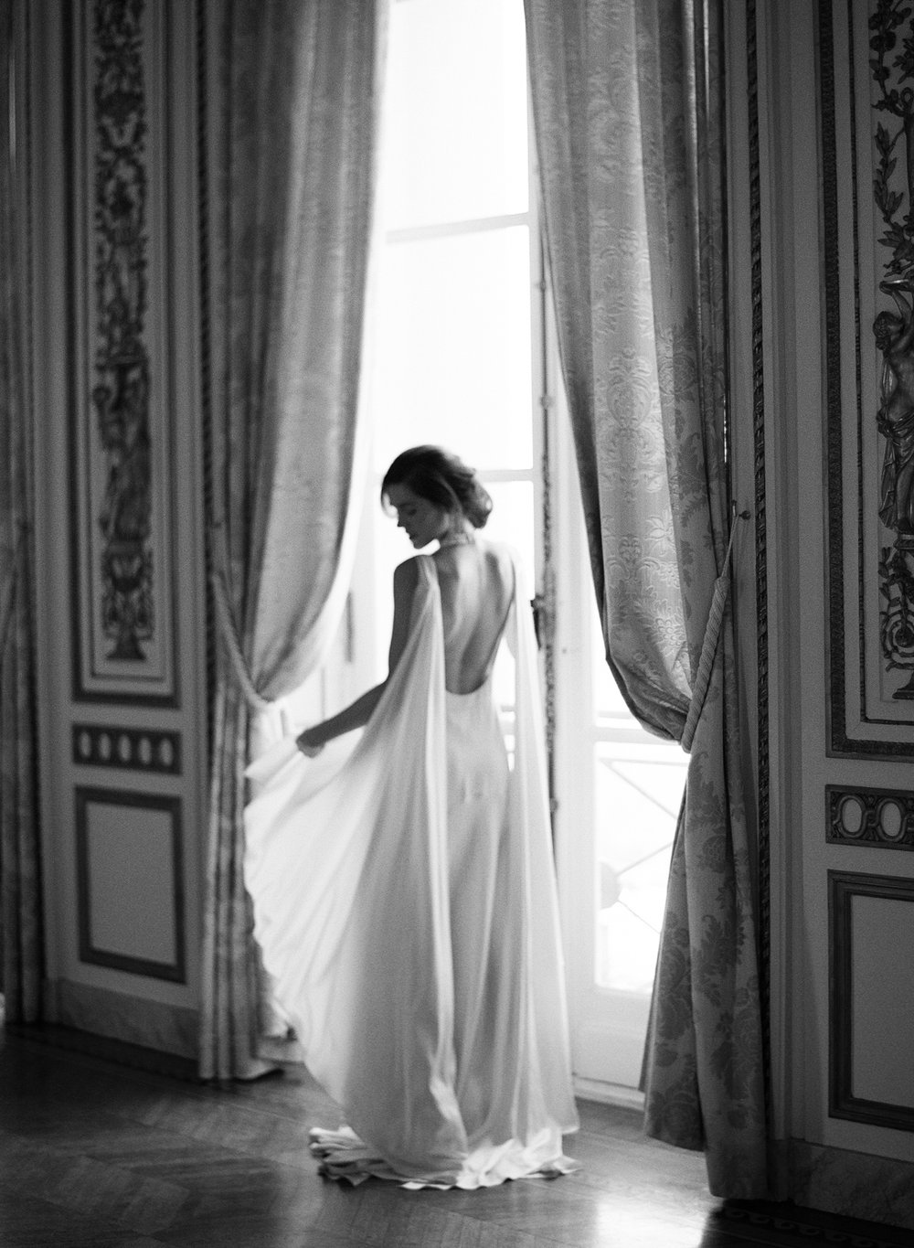Bride in a backless Cortana gown with shoulder trains stands at ballroom windows; Sylvie Gil Photography