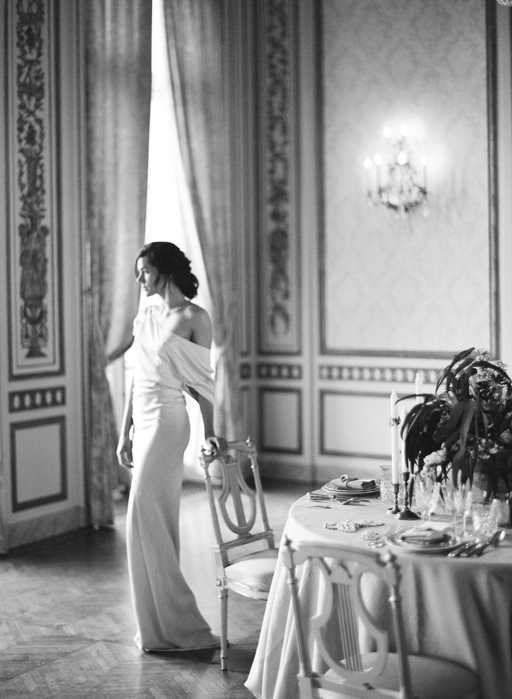 Bride at vintage classic French reception table in an off-the-shoulder asymmetrical wedding gown; Sylvie Gil Photography