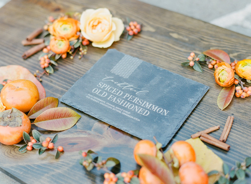 Slate cards engraved with the wedding reception signature cocktail - spiced persimmon old fashioned; Sylvie Gil Photography