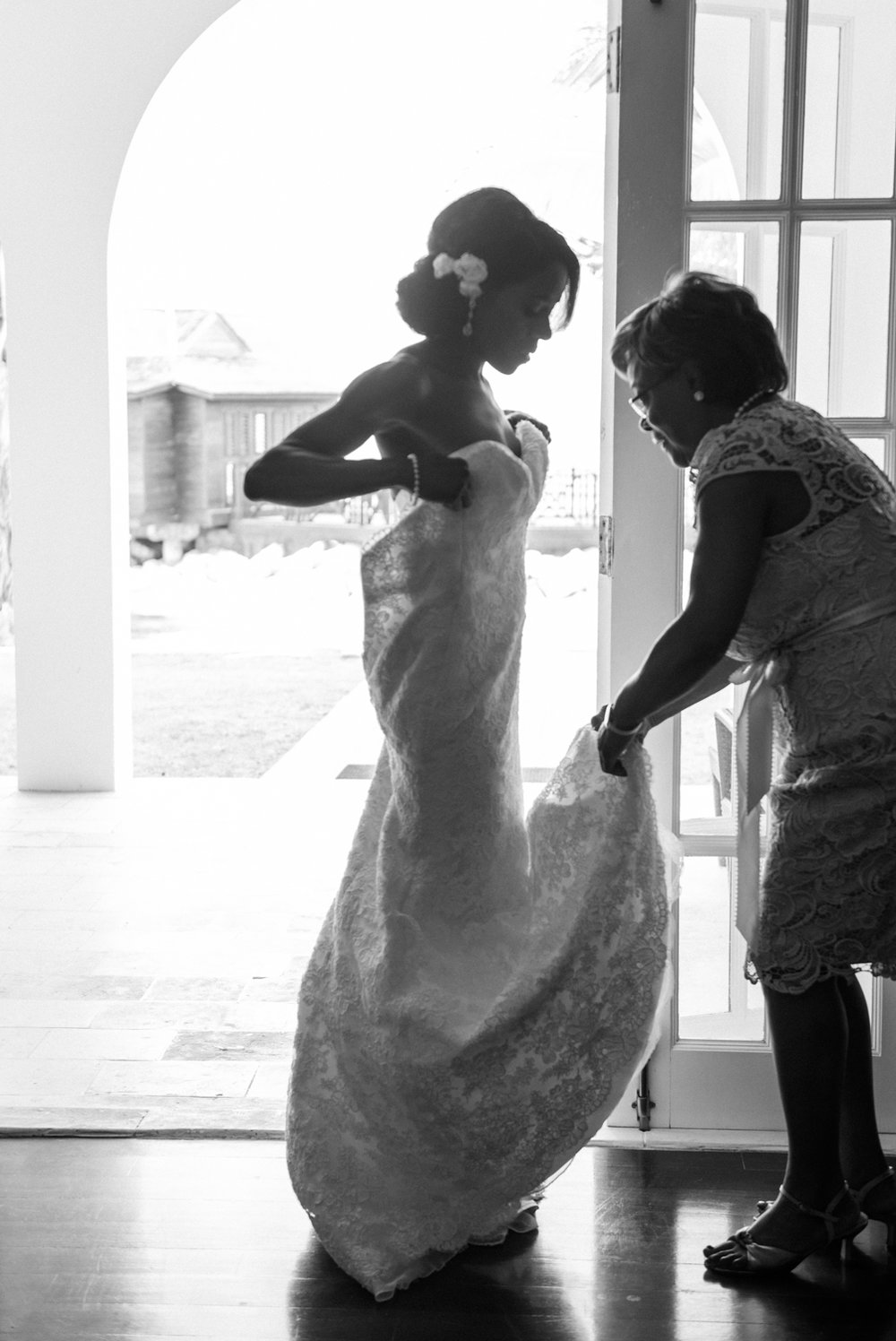Bride's mother helps her put on her lace sweetheart neckline Modern Trousseau gown; Sylvie Gil Photography
