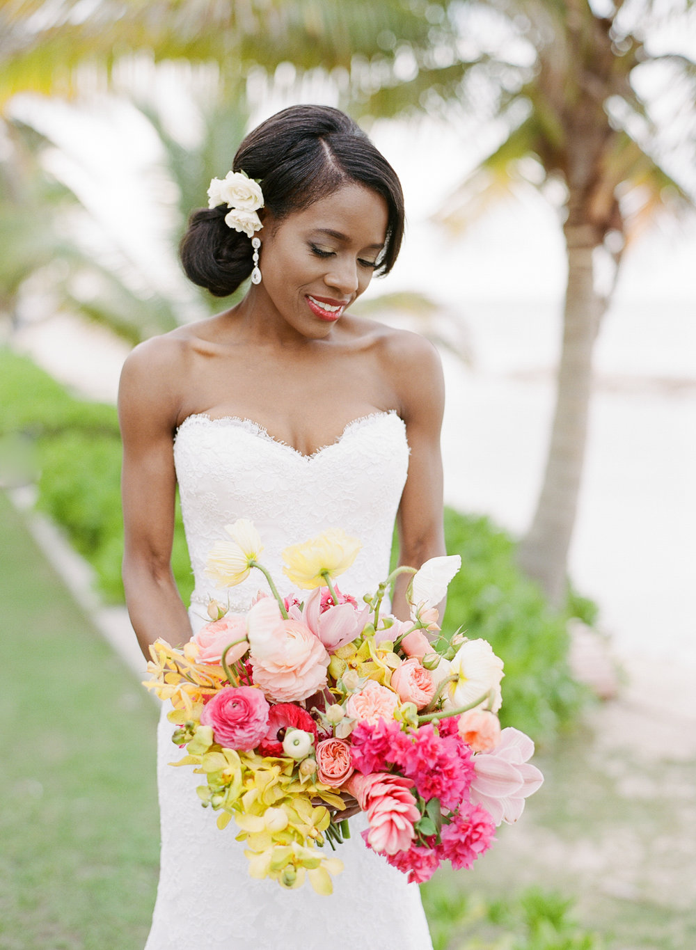Beautiful African American bride with a classic side chignon and colorful tropical bouquet; Sylvie Gil Photography