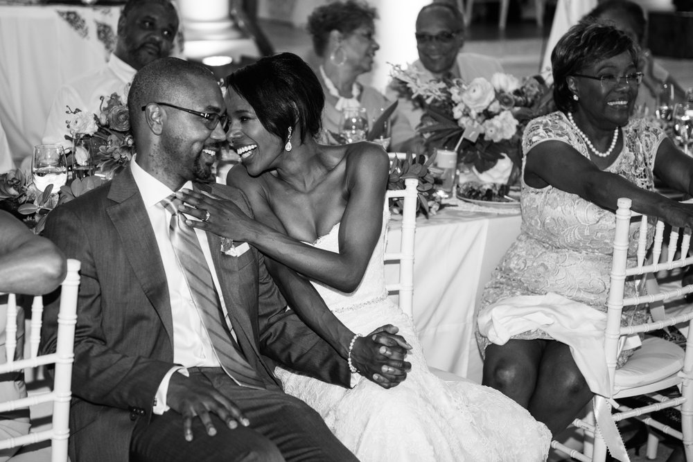 Bride and groom share a sweet moment during toasts at the Montego Bay wedding reception; Sylvie Gil Photography