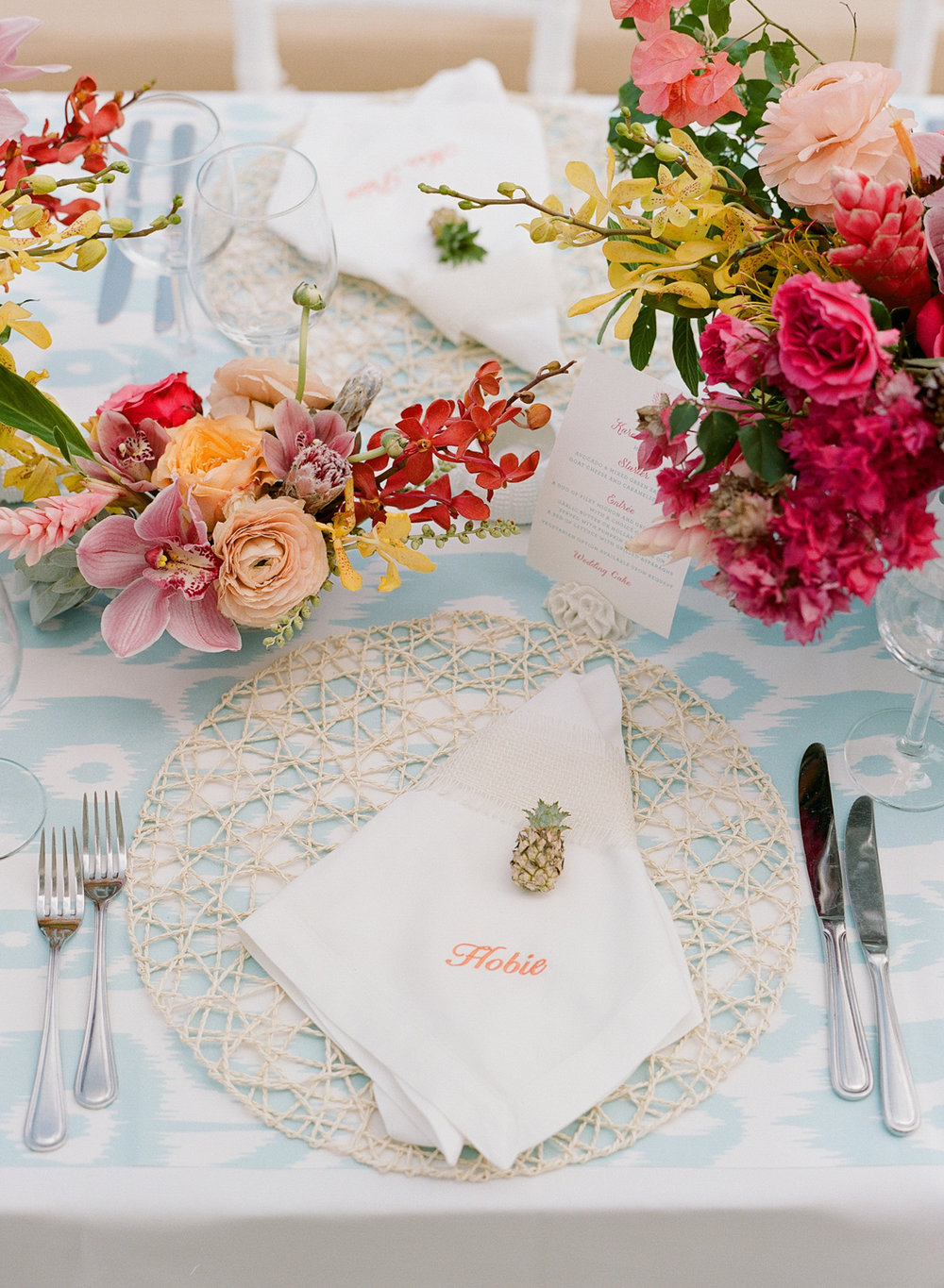 Tiny pineapples and personalized napkins compliment bright floral table settings; Sylvie Gil Photography