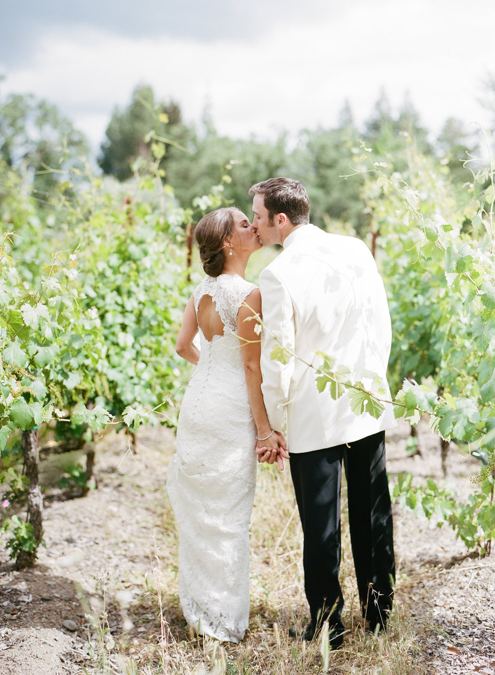 Bride and groom kiss in the vineyards of Vintage Estates, Yountville, CA; Sylvie Gil Photography