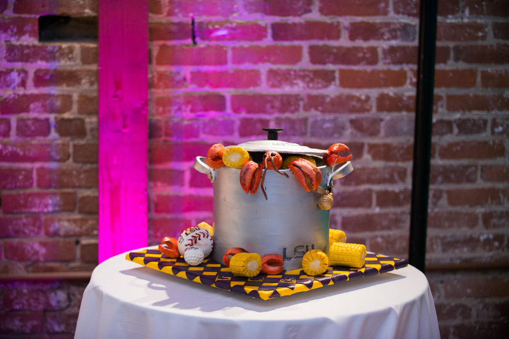 Whimsical groom's cake - a crab boil decorated with cobs of corn and an LSU baseball; Sylvie Gil Photography