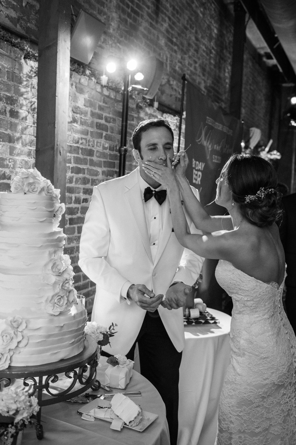 Bride wipes cake off her groom's face during the cake cutting; Sylvie Gil Photography