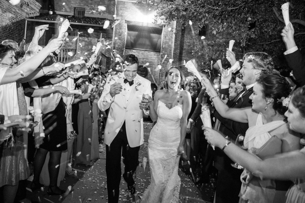 Bride and groom leaving the wedding to showers of confetti from guests; Sylvie Gil Photography