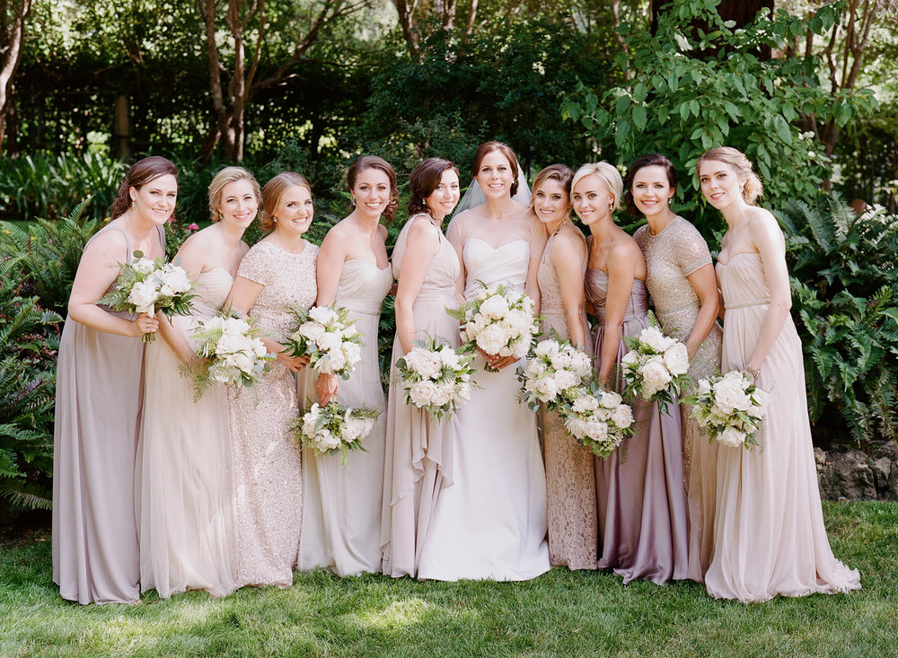 Bride in Vera Wang and bridesmaids in assorted champagne gowns; Sylvie Gil Photography