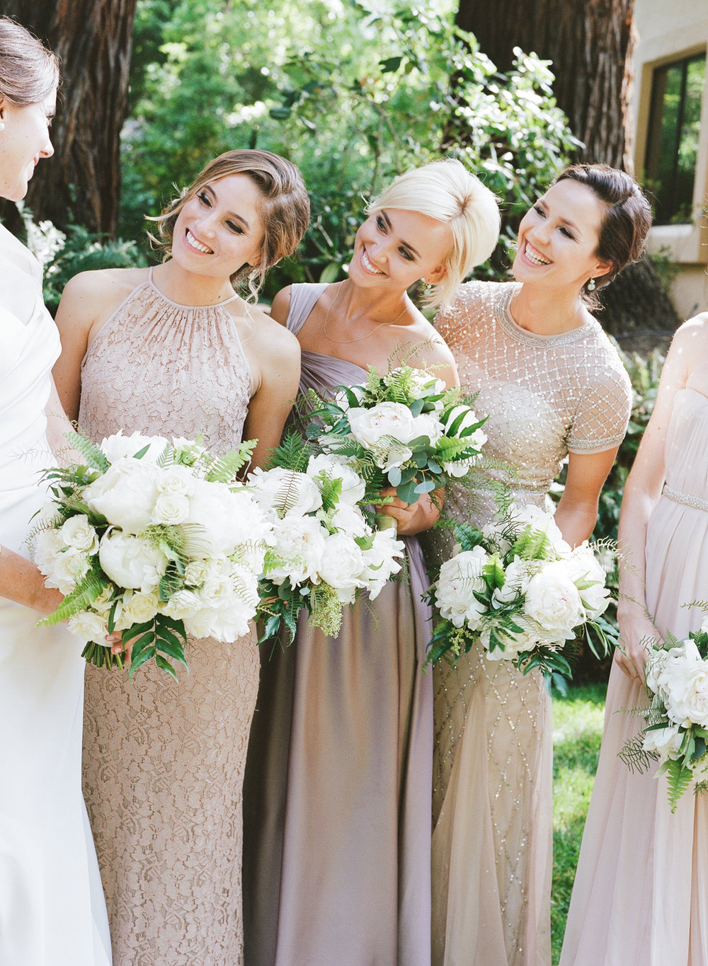 Bridesmaids in nude and champagne dresses hold white floral and fern bouquets; Sylvie Gil Photography
