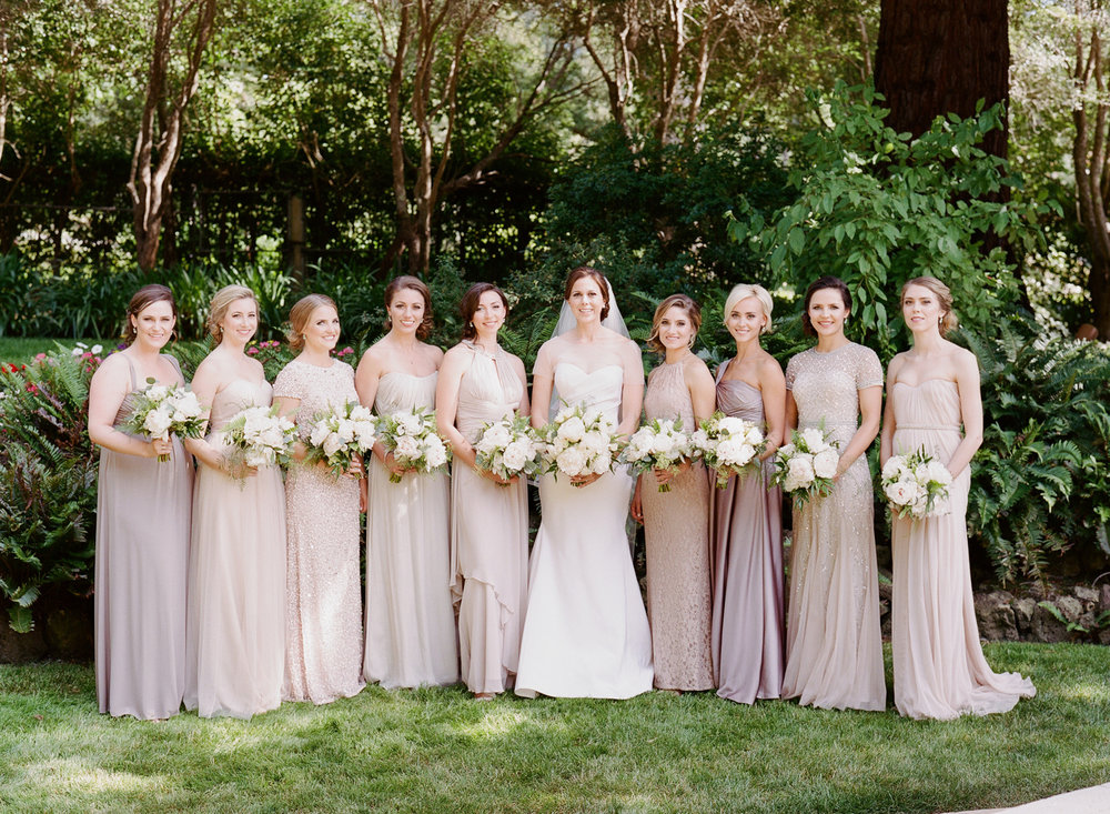 The bride and nine bridesmaids in mix and match champagne gowns; Sylvie Gil Photography