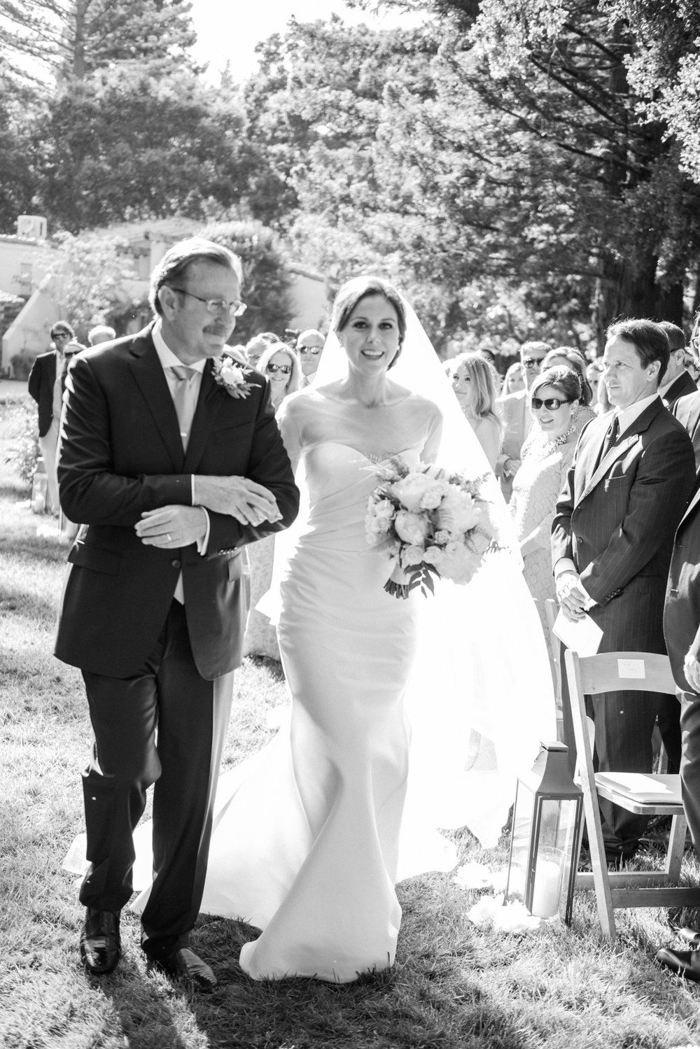 The bride's father walks her down the aisle during the ceremony at a private residence in Woodside, California; Sylvie Gil Photography