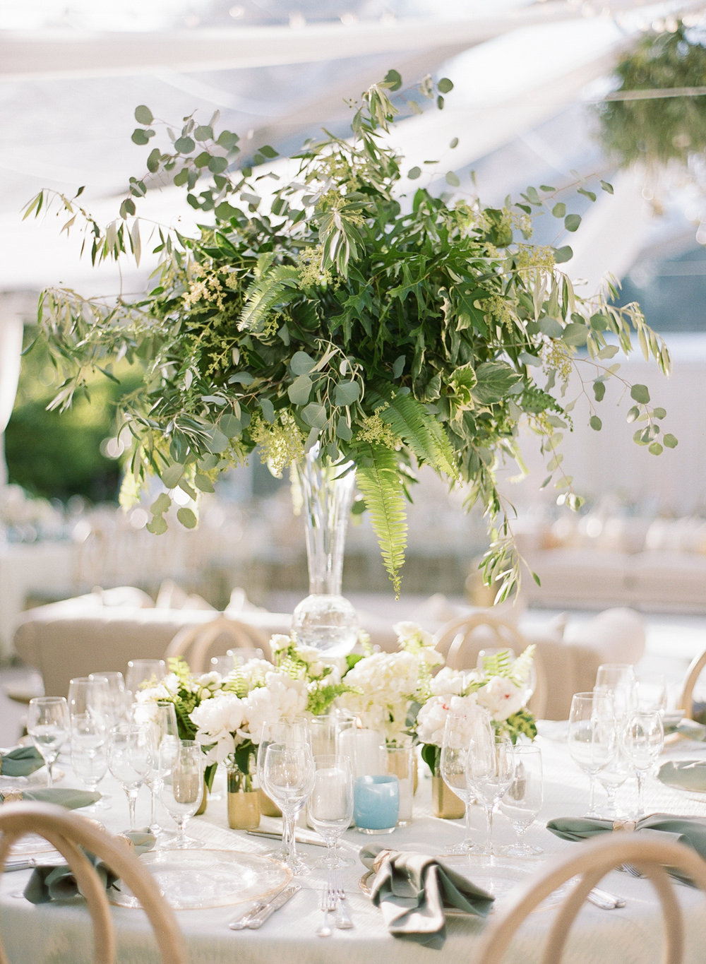 Tall leafy centerpieces made with ferns and eucalyptus on reception tables; Sylvie Gil Photography