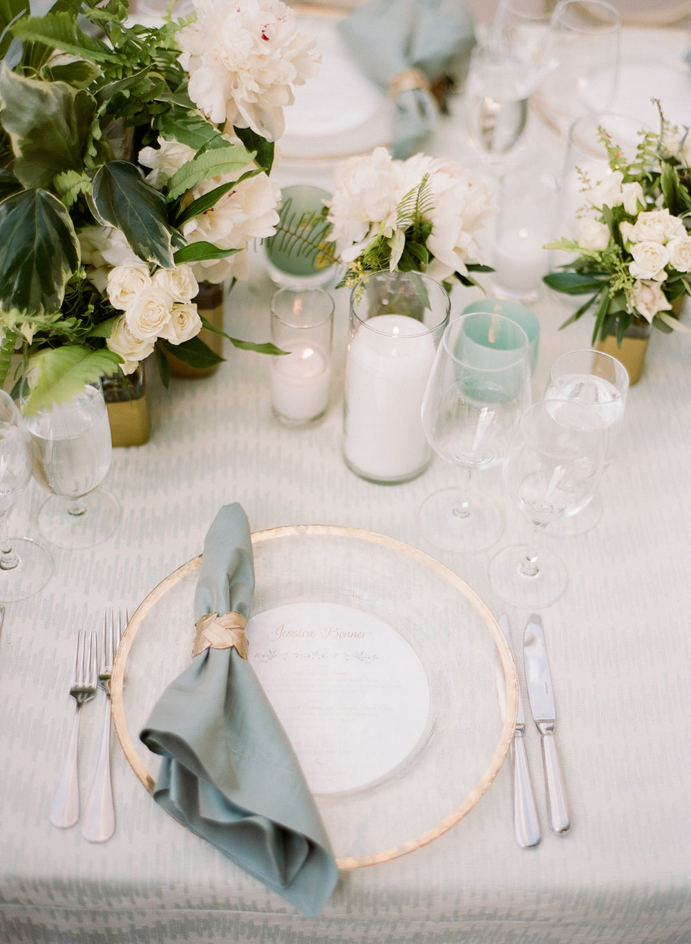 Glass table settings r trimmed in gold, with sea foam napkins and white floral centerpieces; Sylvie Gil Photography