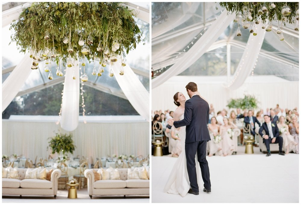 Leafy fern wreath hangs from reception tent, bride and groom share their first dance; Sylvie Gil Photography