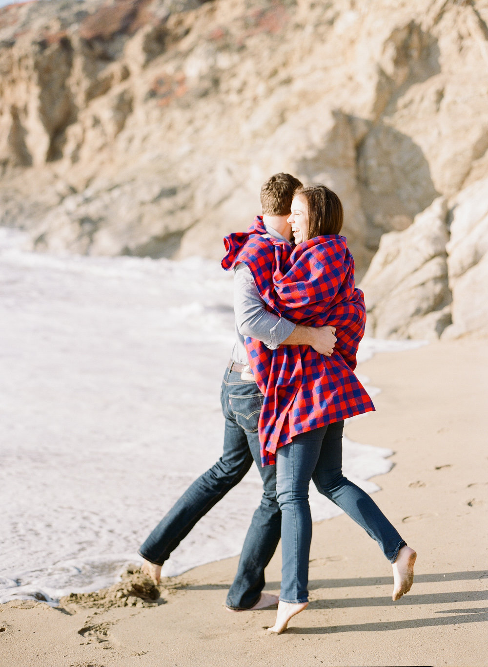 Couple laughs on the beach during engagement session; Sylvie Gil Photography