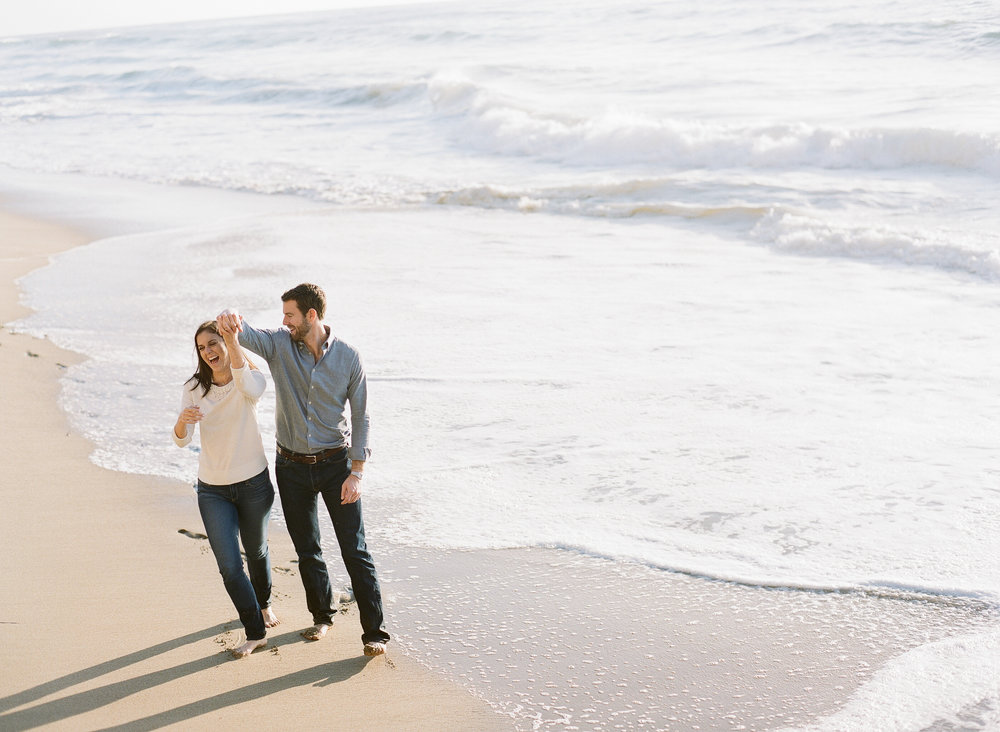 Couple dances on beach during Northern California engagement session; Sylvie Gil Photography