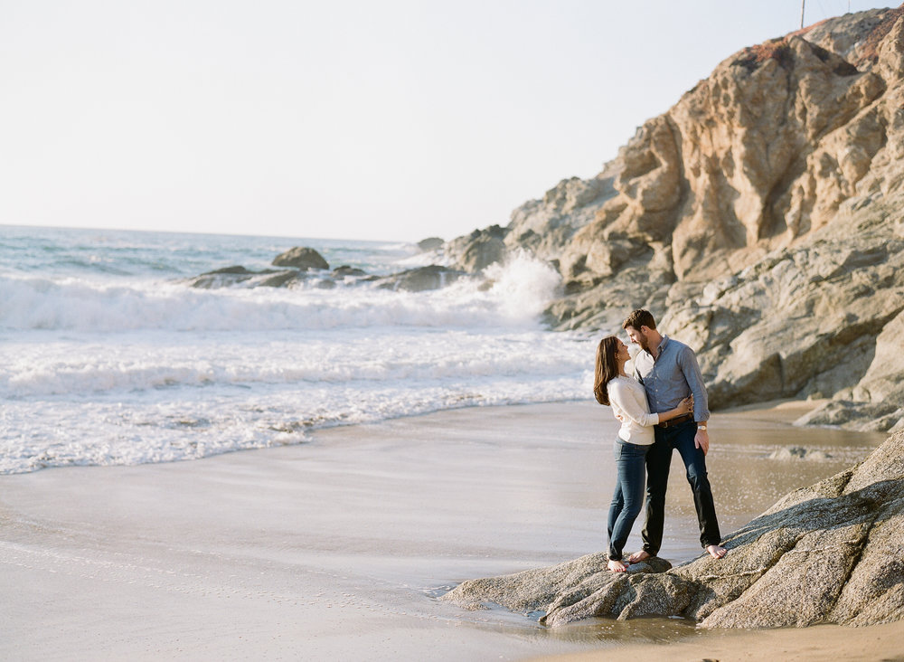 Couple stands on Northern California beach during engagement session; Sylvie Gil Photography
