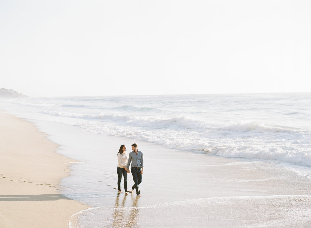 Couple walks along the beach holding hands during engagement session photo shoot; Sylvie Gil Photography