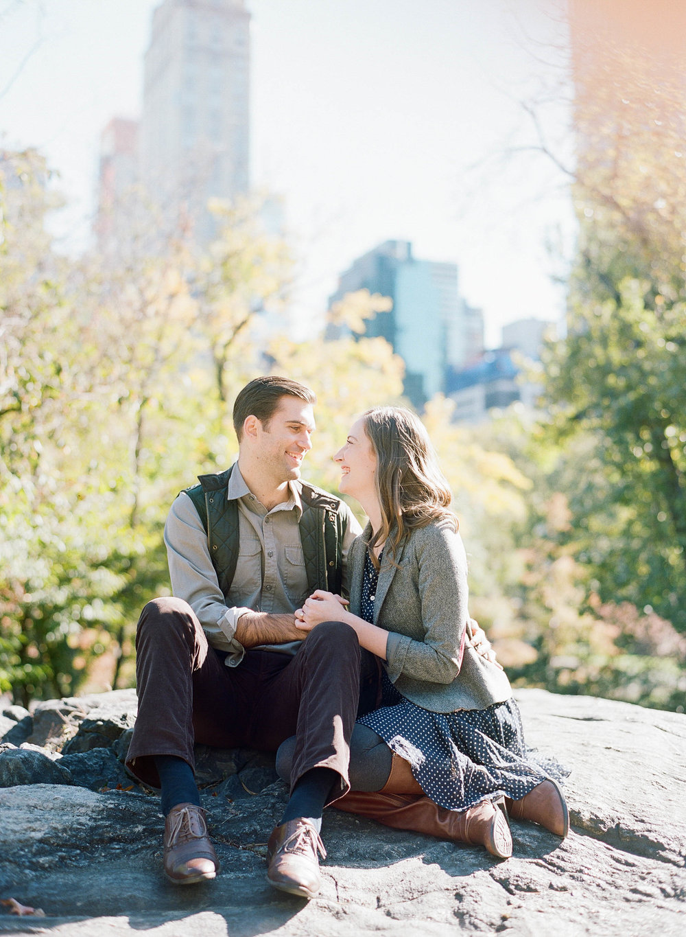 Couple laughs together during engagement session in Central Park, New York City; Sylvie Gil Photography