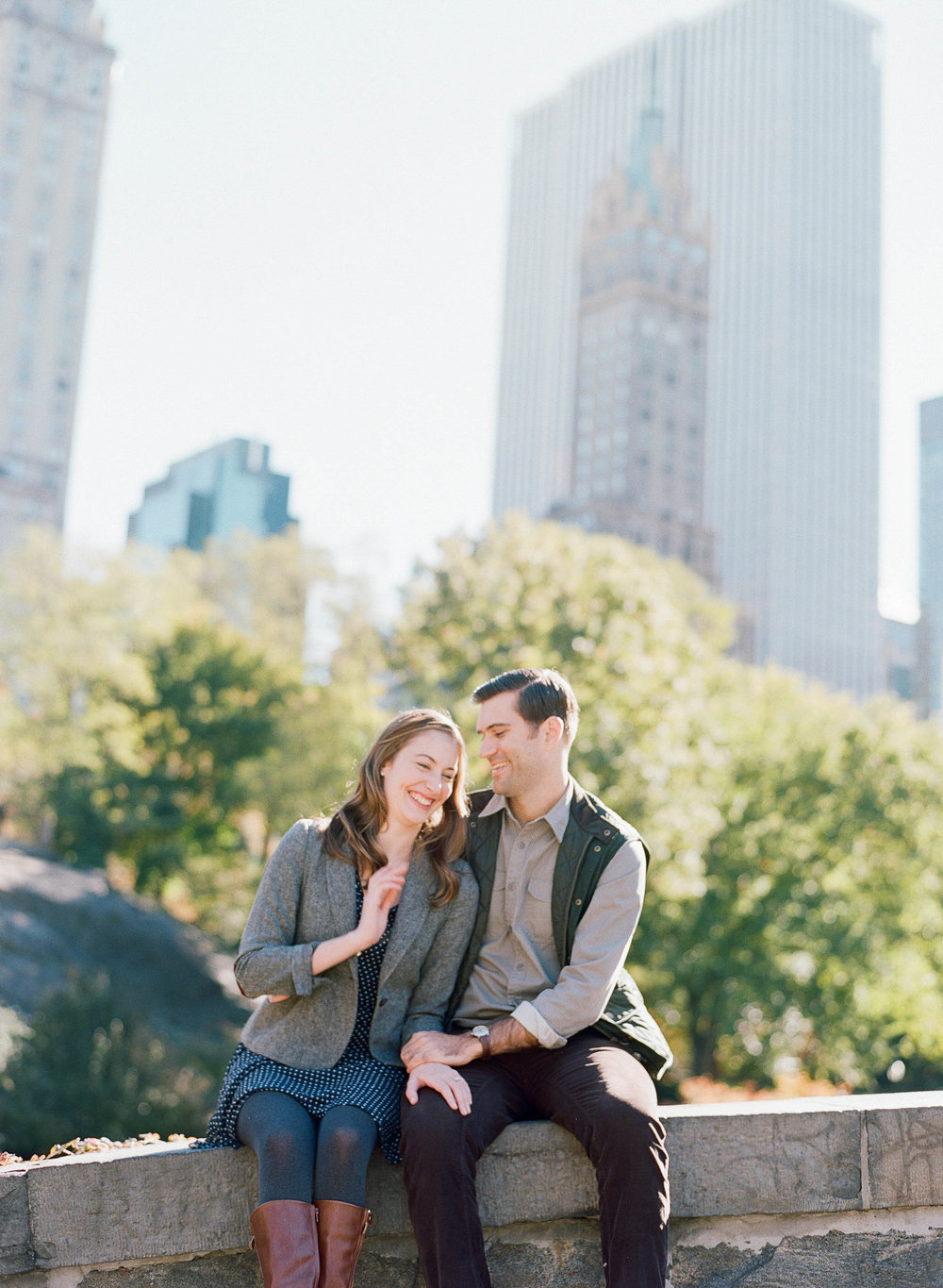 Couple shares a laugh sitting on a bridge in Central Park, New York City during a late summer engagement session; Sylvie Gil Photography