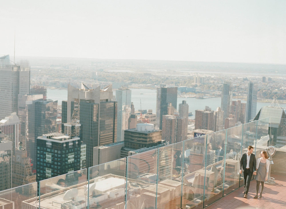 Couple walks on the viewing deck of a skyscraper in New York City during a fall engagement session; Sylvie Gil Photography