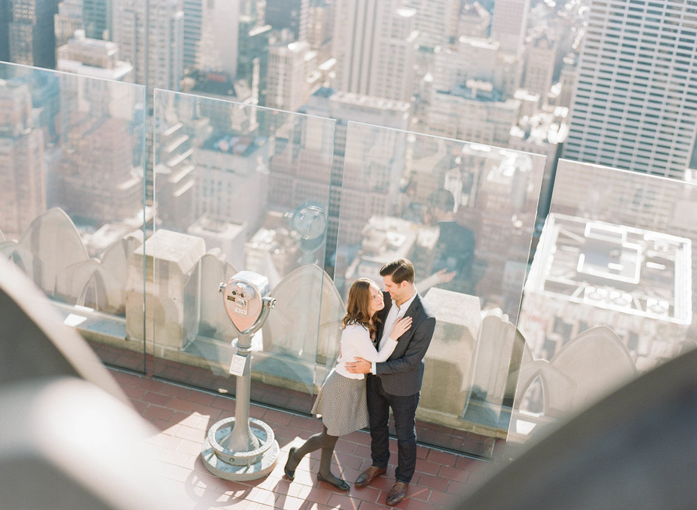 Couple next to a telescope on the roof a New York skyscraper during an engagement session; Sylvie Gil Photography