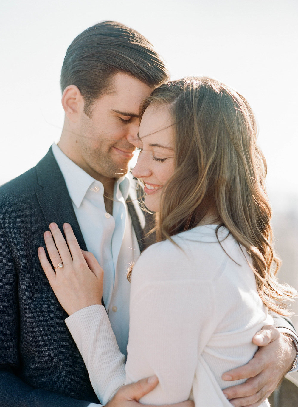 Fiancees share a hug during an autumn engagement session on the roof of a midtown New York City skyscraper; Sylvie Gil Photography