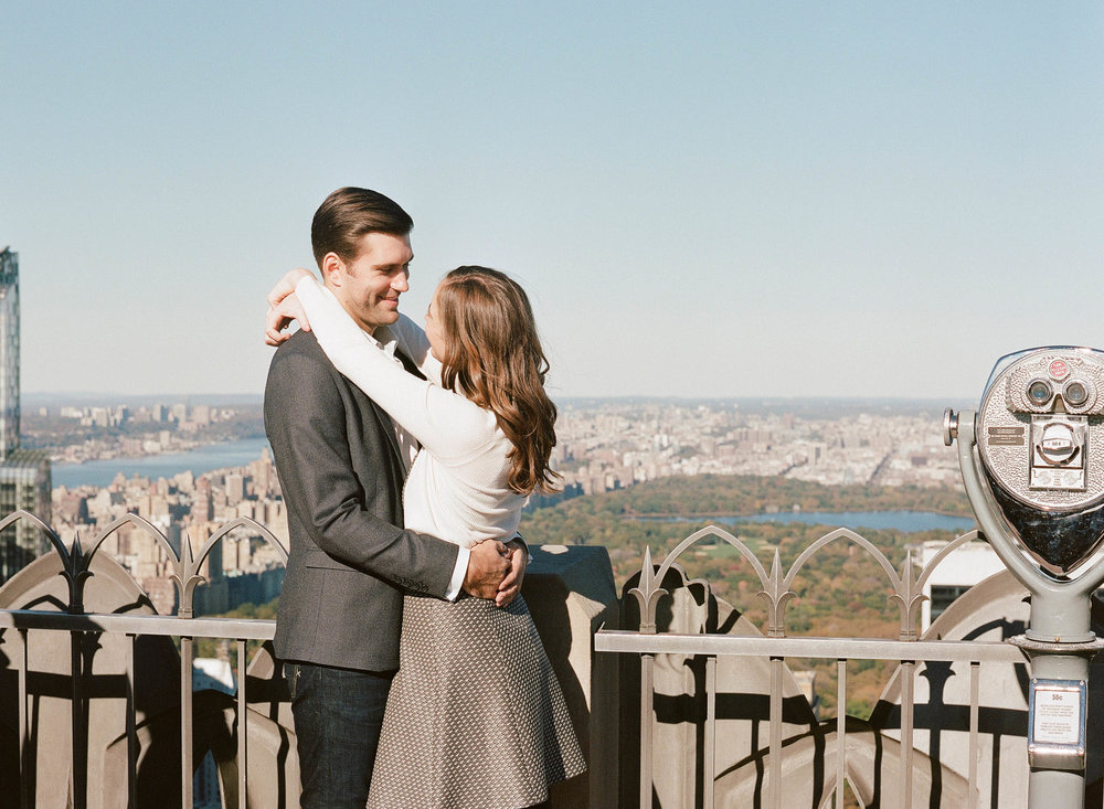Couple smiles at each other in front of a view of Manhattan and Central Park; Sylvie Gil Photography