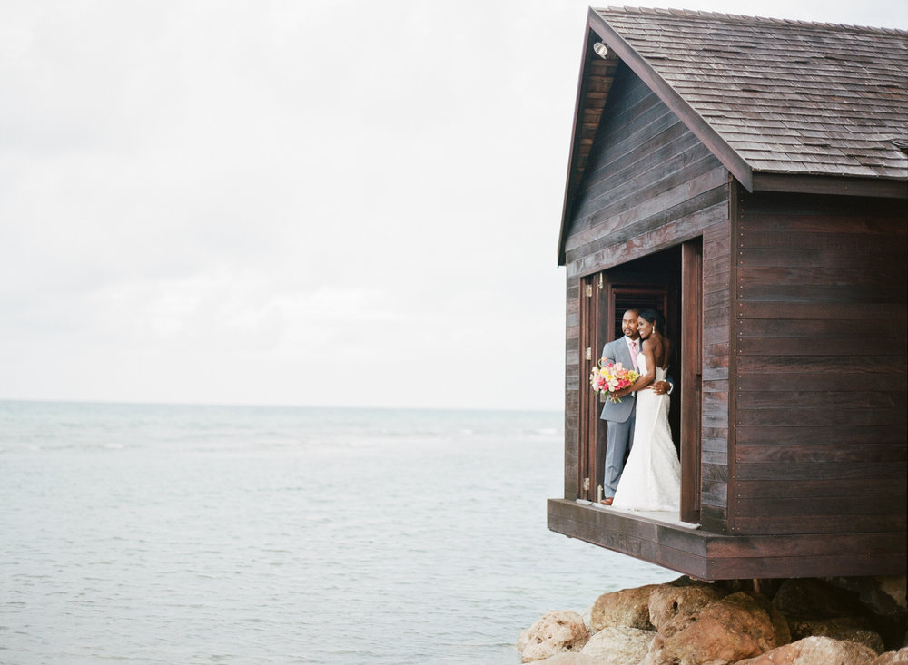 Bride and groom looks out at the ocean in Montego Bay, Jamaica; Sylvie Gil Photography