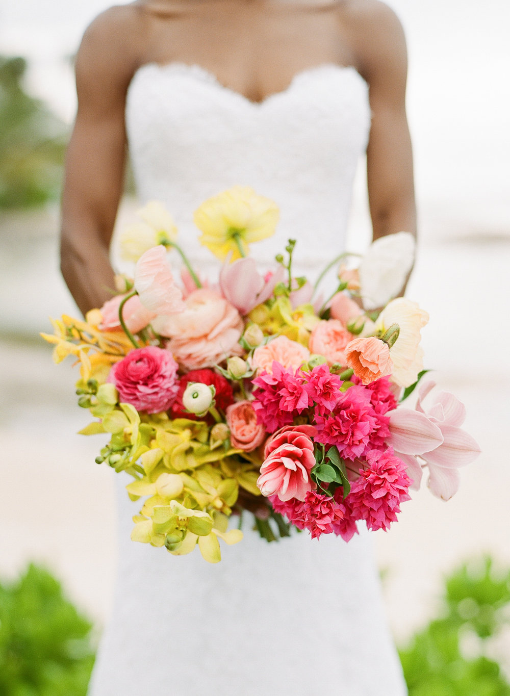 Bride in a lace, sweetheart neckline gown with a pink, yellow, and salmon orchid bouquet; Sylvie Gil Photography