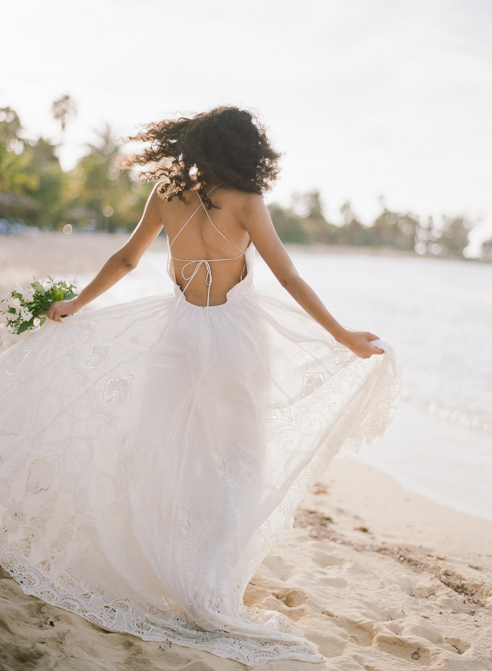 Caribbean bride spins in a flowy, backless gown on the beach; Sylvie Gil Photography