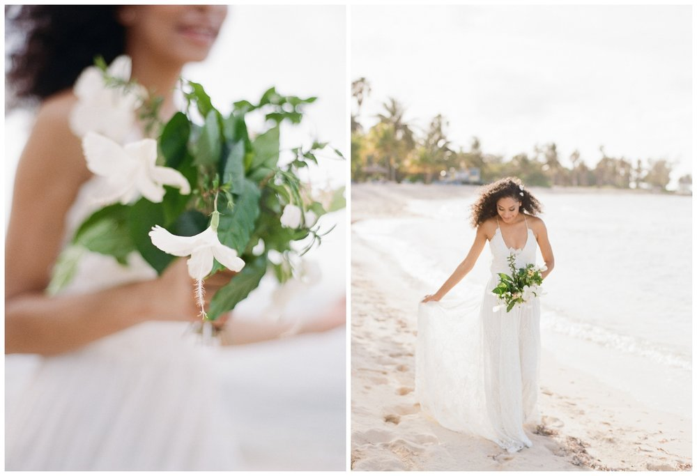 Caribbean bride walks along the beach with her tropical hibiscus bouquet; Sylvie Gil Photography
