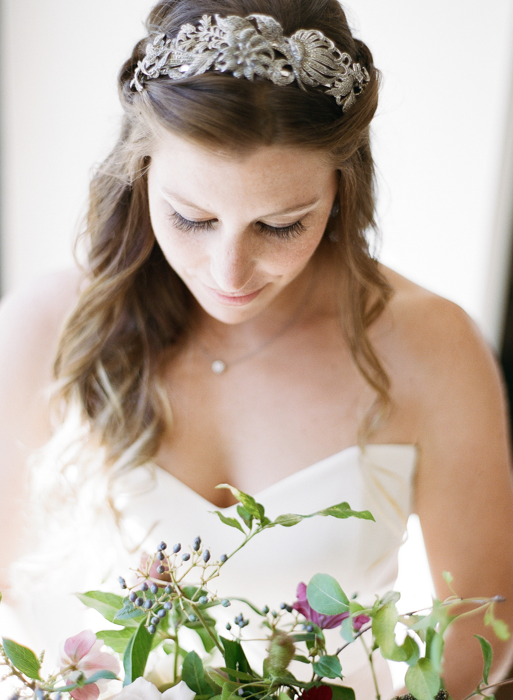 The bride gazes down at her eclectic bouquet, wearing a gorgeous bohemian metallic headpiece