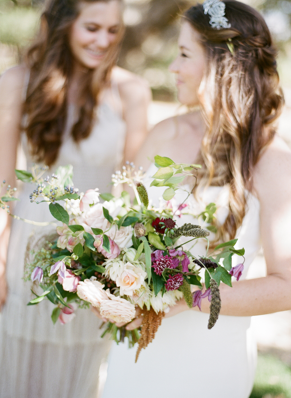 Tali's earthy, wild bouquet features a variety of florals all spilling out of her hands in a cascade; photo by Sylvie Gil