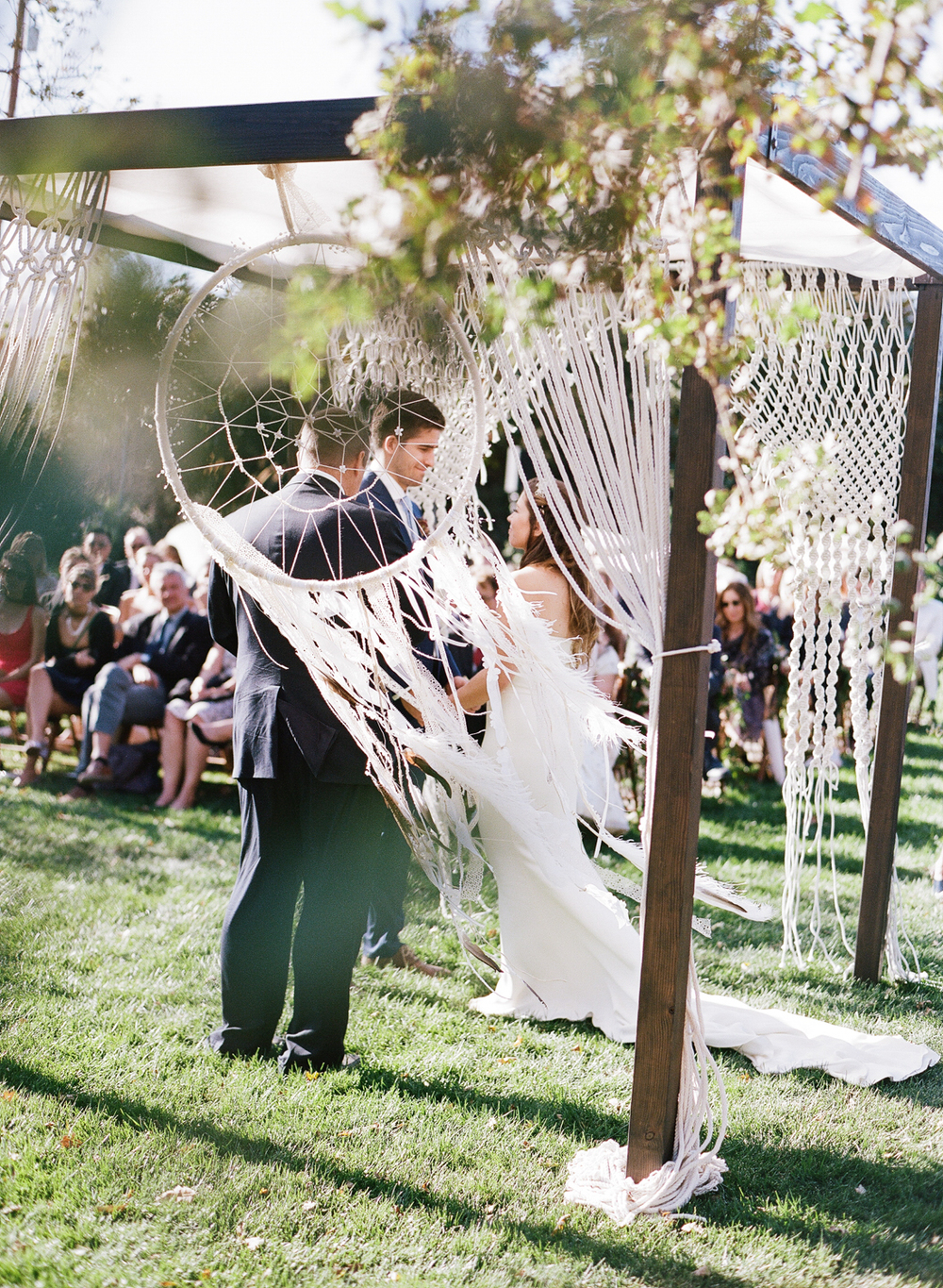 The dreamy macrame ceremony space creates a romantic vibe as the couple exchanges vows; photo by Sylvie Gil