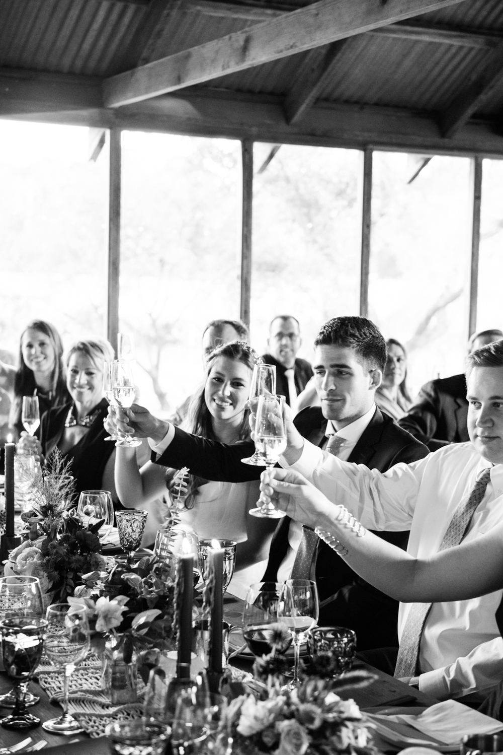 The bride and groom raise their glasses in a toast during their barn reception; photo by Sylvie Gil